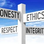 """White wooden signpost with four arrows - """"honesty"""", """"ethics"""", """"respect"""", """"integrity""""."""